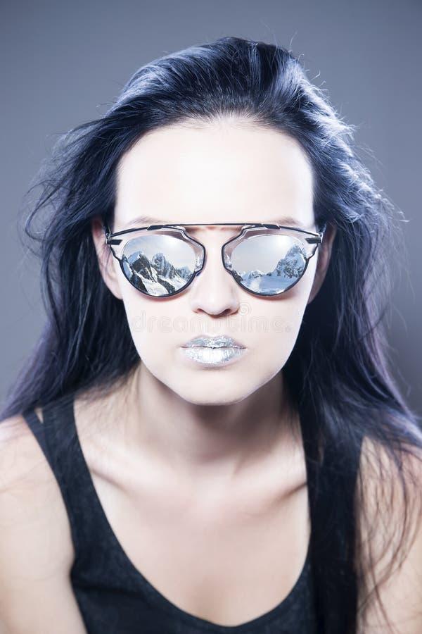 Retrato bonito do modelo de forma da mulher nos óculos de sol com reflexões das montanhas e dos bordos de prata metálicos Pentead imagem de stock