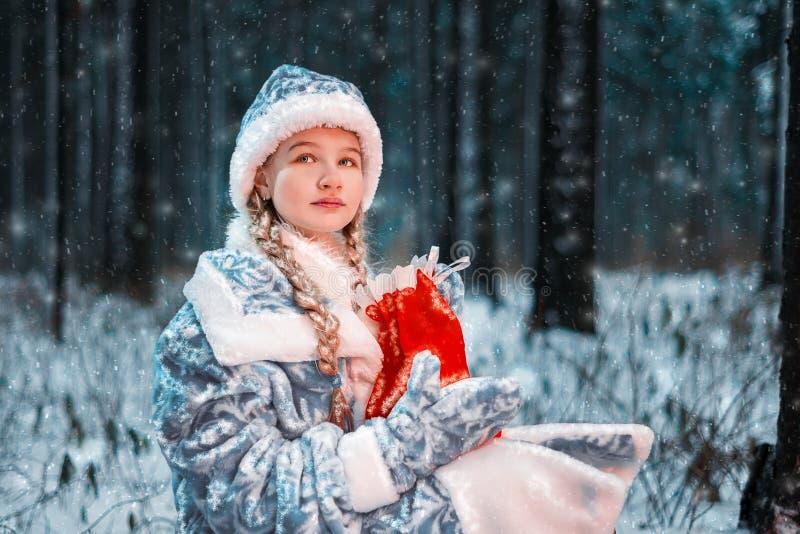 Retrato bonito do Natal da donzela da neve menina apenas em uma floresta fria com presentes imagem de stock