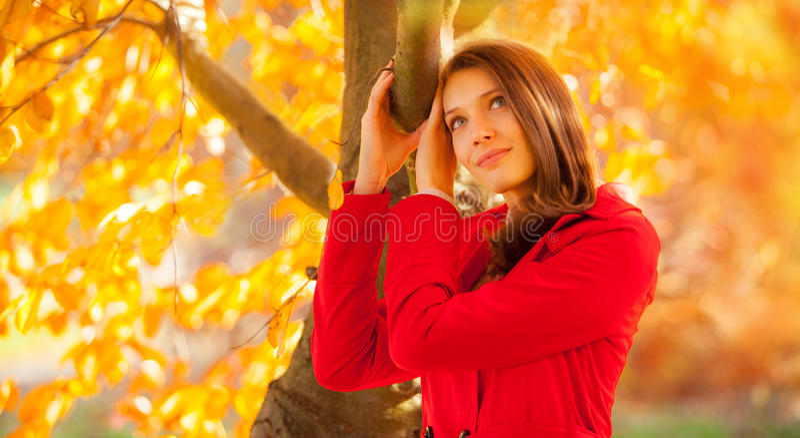 Retrato bonito do outono da jovem mulher com revestimento vermelho imagem de stock royalty free
