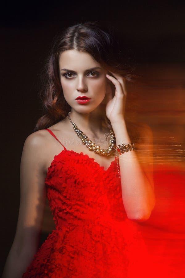 Retrato borroso del arte del color de una muchacha en un fondo oscuro Forme a la mujer con maquillaje hermoso y un vestido ligero fotografía de archivo