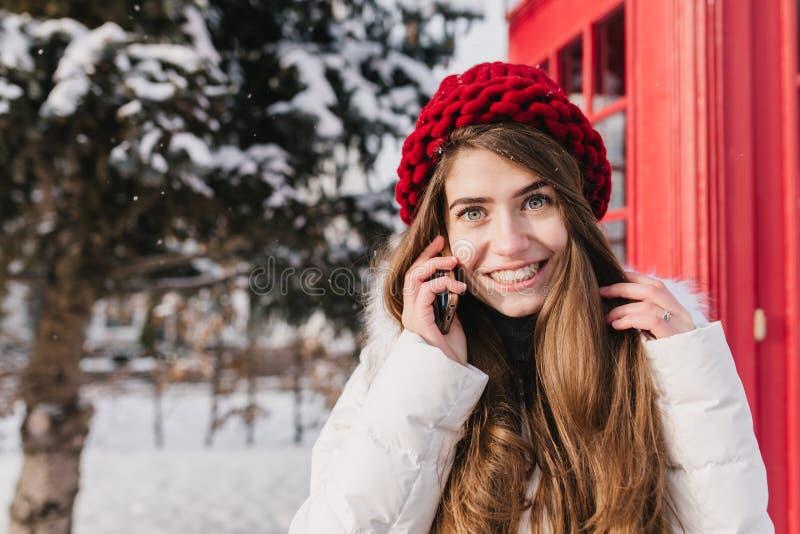 Retrato británico elegante de sorprender a la mujer joven con el pelo moreno largo en sombrero rojo que habla en el teléfono en l imagen de archivo