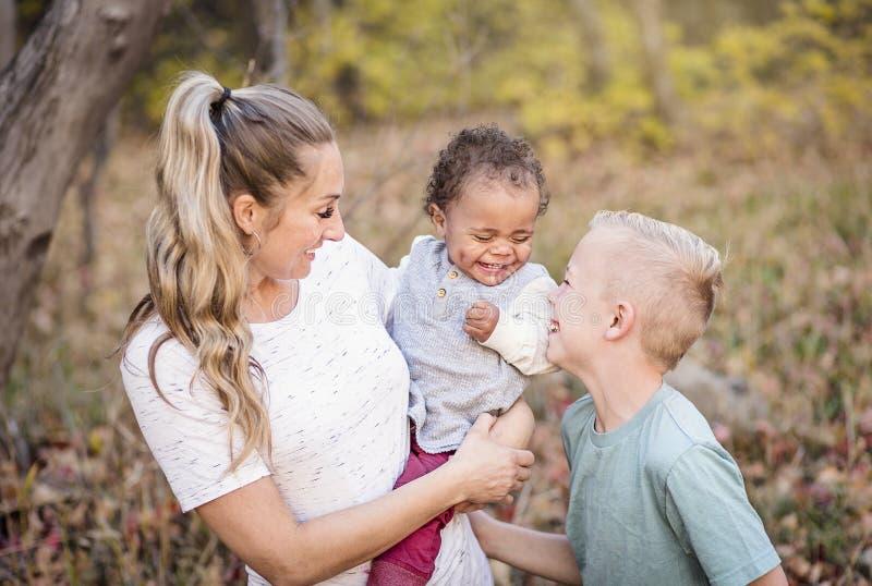 Retrato cândido bonito de uma mãe que joga com seus filhos bi-raciais bonitos foto de stock