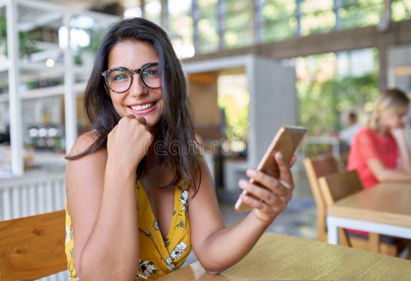 Retrato cândido do estilo de vida de rir o estudante milenar latino-americano que datilografa no telefone celular no café na moda imagens de stock royalty free