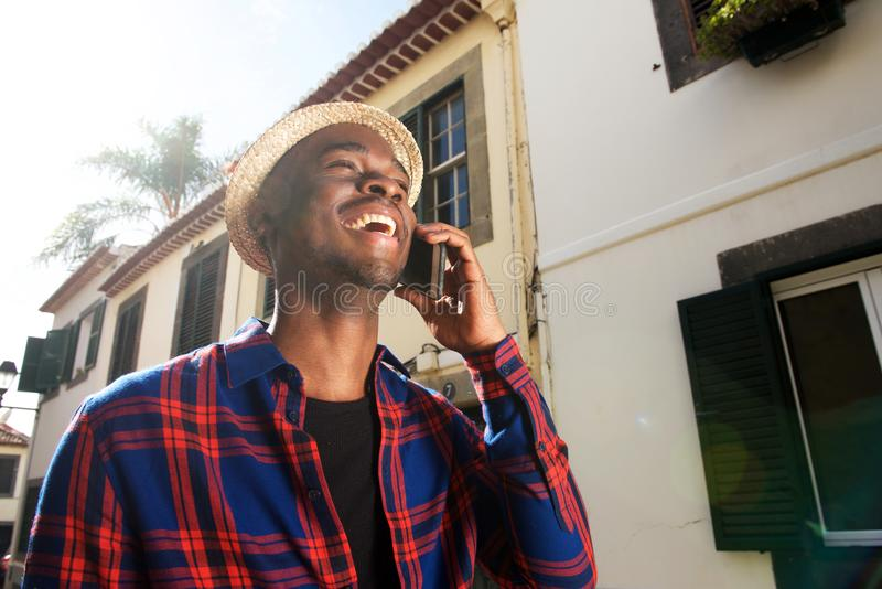 Retrato cândido do homem afro-americano feliz que fala com telefone celular fotografia de stock