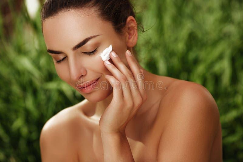 Retrato calmo natural de uma menina bonita com a pele pura que faz o skincare com nata fora fotos de stock royalty free