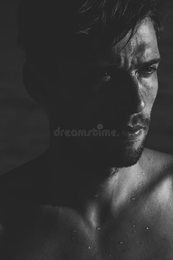 Retrato cambiante oscuro de un hombre joven intenso imagenes de archivo