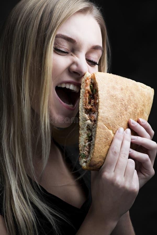 Retrato carismático de una mujer joven con los alimentos de preparación rápida imágenes de archivo libres de regalías