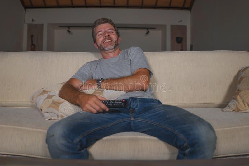 Retrato casero de la forma de vida de la demostración joven de la televisión del hombre feliz y atractivo o de la risa cómica de  imagen de archivo