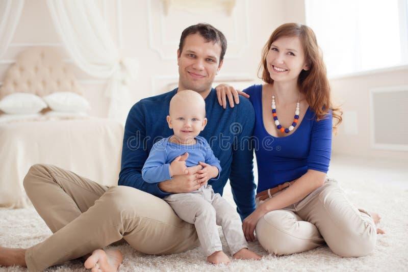 Retrato casero de una familia joven feliz foto de archivo
