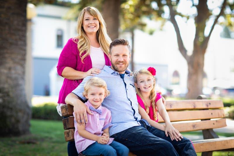 Retrato caucásico de la familia de los jóvenes atractivos felices en el parque imagen de archivo