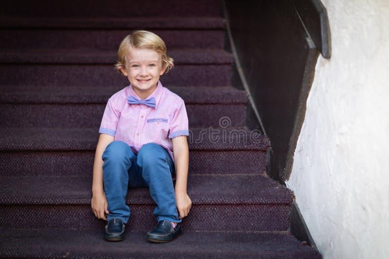 Retrato caucásico joven lindo del muchacho que se sienta en pasos de la escalera imagen de archivo