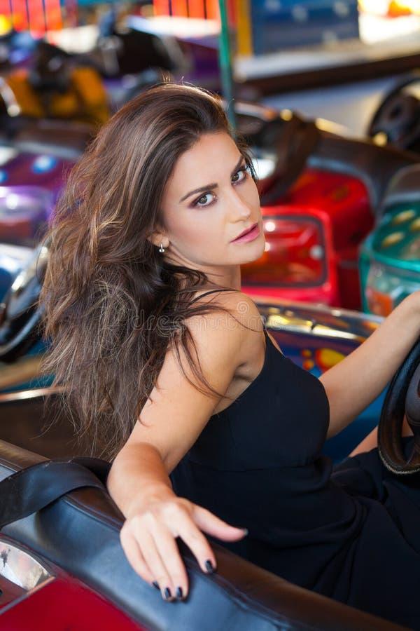 Retrato caucásico moreno joven atractivo de la mujer en parque de atracciones en día de verano del coche imagen de archivo libre de regalías
