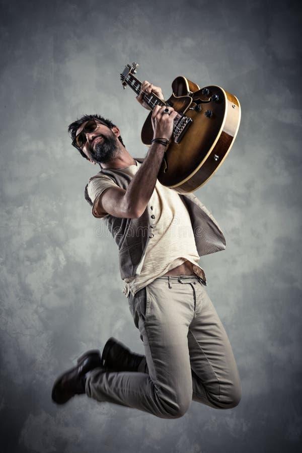 Retrato caucasiano adulto do guitarrista que joga a guitarra elétrica e que salta no fundo do grunge Conceito moderno do cantor d imagens de stock royalty free