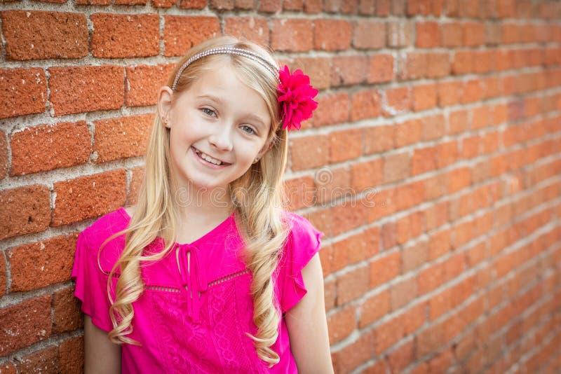 Retrato caucasiano novo bonito da menina contra uma parede de tijolo imagem de stock royalty free