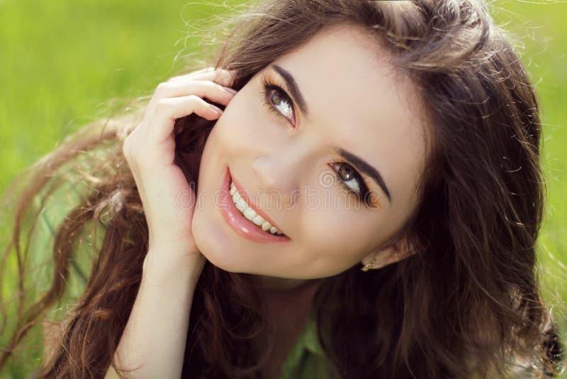 Retrato cercano de la mujer joven hermosa en hierba verde en su fotografía de archivo libre de regalías