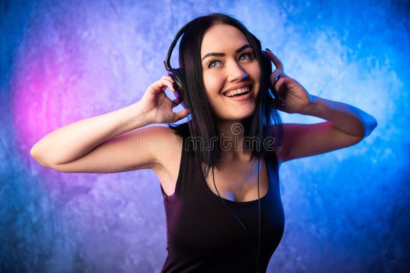 Retrato cercano de los auriculares de DJ de la chica joven que lleva atractiva imágenes de archivo libres de regalías