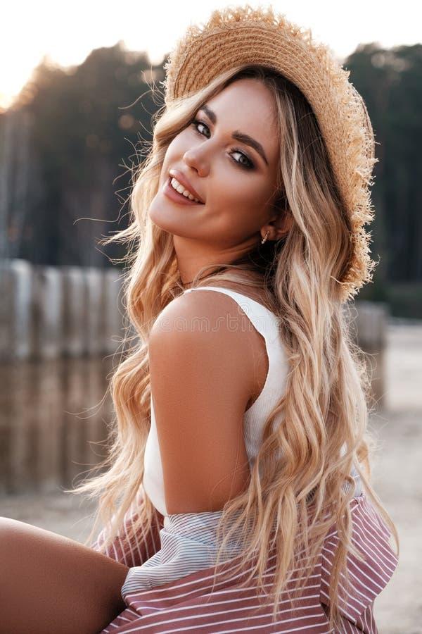 Retrato cercano de una muchacha bonita, romántica y alegre del país con el pelo flojo largo en un sombrero de paja Luz del sol, c foto de archivo