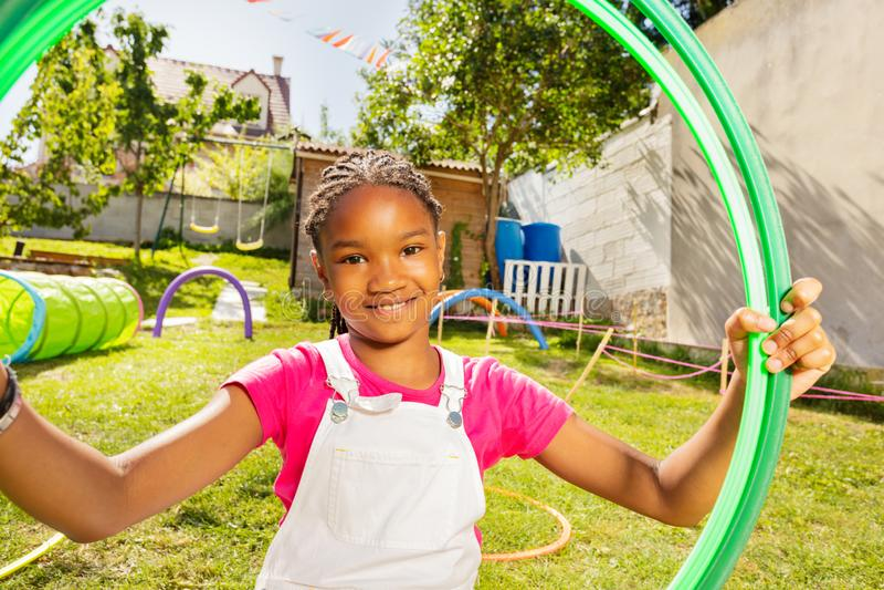 Retrato cercano de una niña en el patio de juegos con aros fotos de archivo