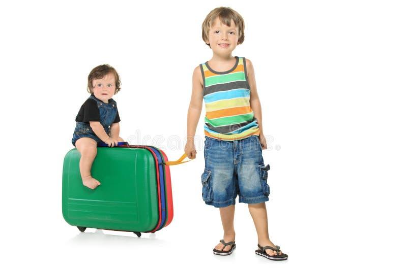 Retrato cheio do comprimento de um menino que puxa uma mala de viagem imagem de stock royalty free
