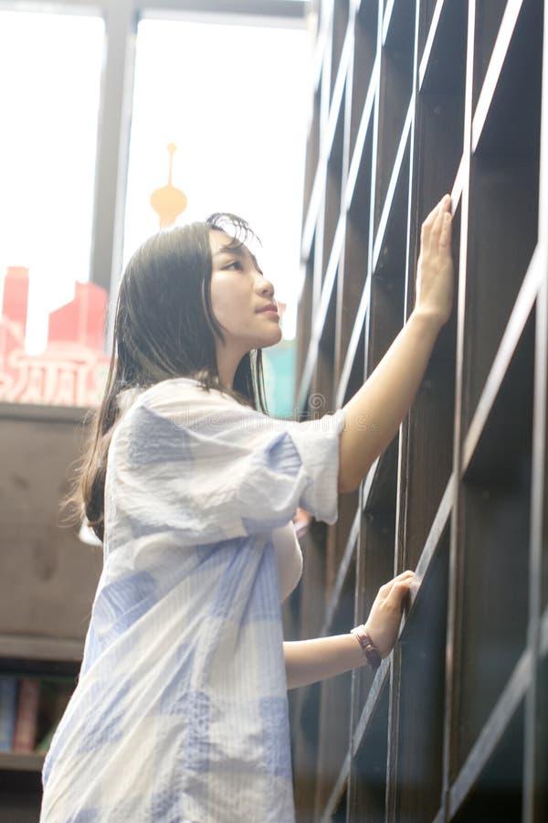 Retrato chinês da mulher bonita nova que alcança para um livro da biblioteca na livraria foto de stock royalty free