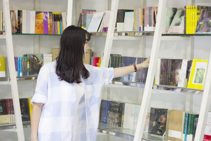 Retrato chinês da mulher bonita nova que alcança para um livro da biblioteca na livraria fotografia de stock