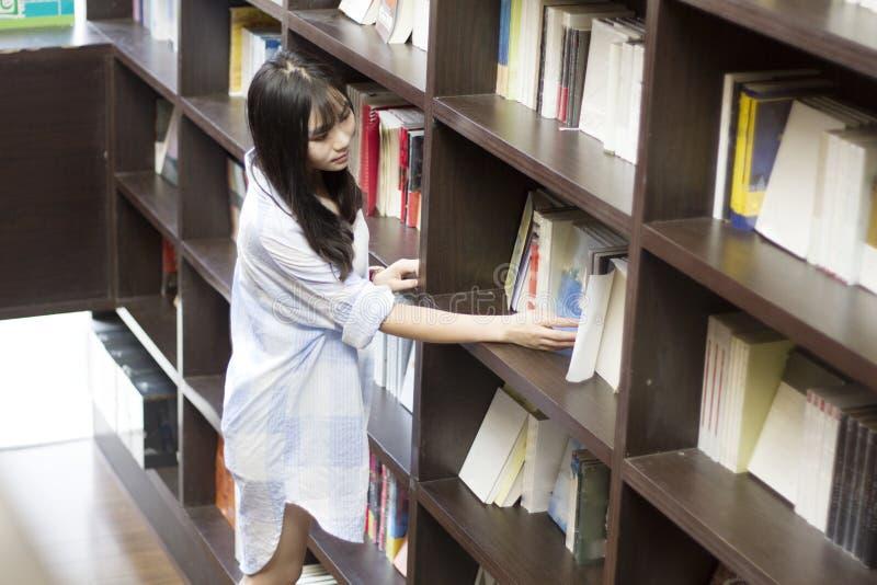 Retrato chinês da mulher bonita nova que alcança para um livro da biblioteca na livraria fotos de stock