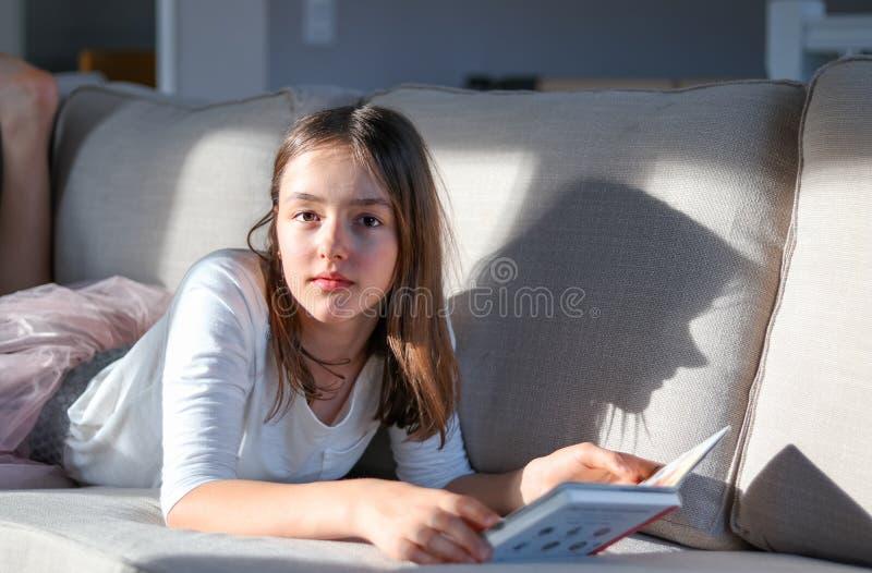 Retrato claro duro da menina bonito do tween que encontra-se no sofá com o livro que olha a câmera com sombra engraçada no sofá imagem de stock royalty free