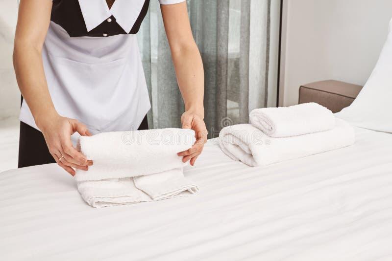 Retrato colhido de toalhas do rolamento do housecleaner na cama ao limpar o quarto e ao preparar tudo para clientes a fotos de stock royalty free