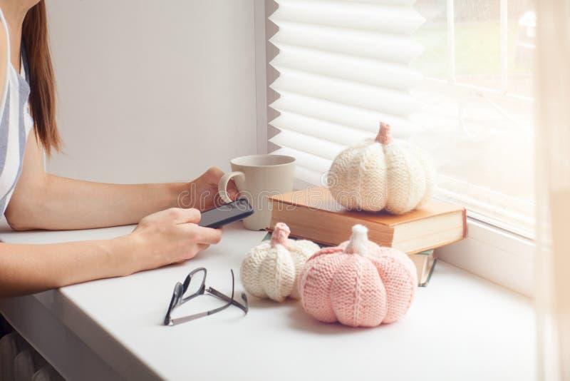 Retrato colhido do chá bebendo ou do café da jovem mulher impressionante, olhando pensativo, sentando-se pela grande janela na ta foto de stock