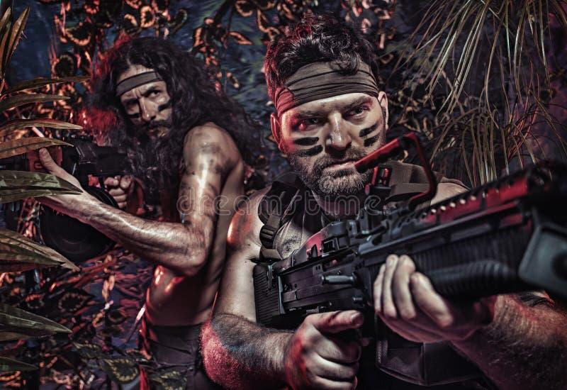 Retrato colorido de dois soldados sérios que lutam no jung fotografia de stock royalty free