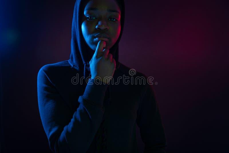 Retrato colorido de uma mulher africana segura com o hoodie vestindo da pele escura imagem de stock