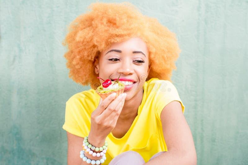 Retrato colorido de una mujer africana con el postre dulce imágenes de archivo libres de regalías