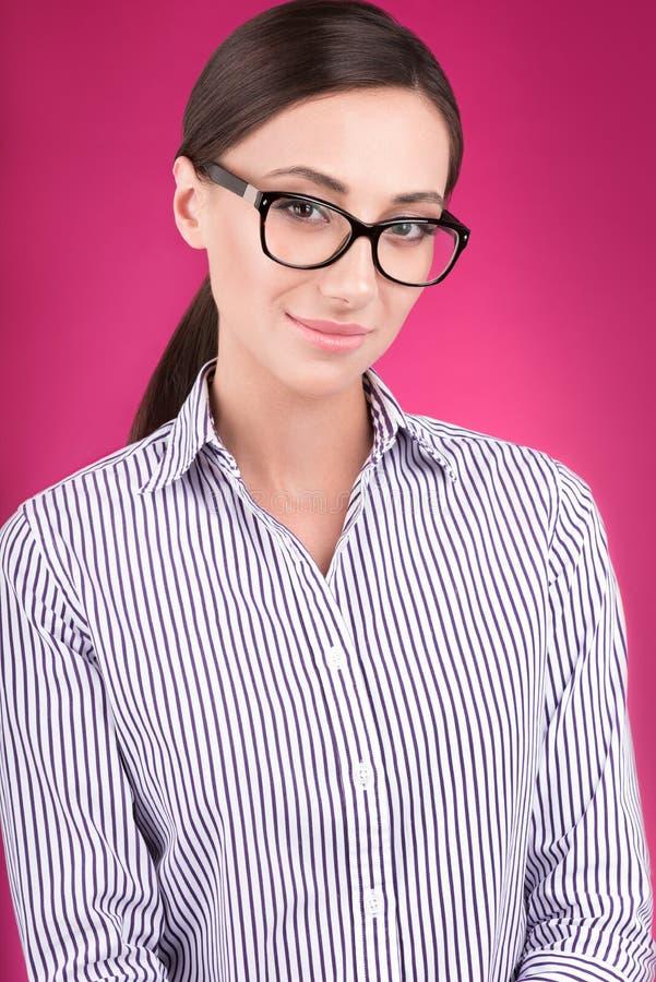 Retrato colorido del estudio de mujeres atractivas jovenes en puntos contra el fondo rosado fotos de archivo libres de regalías