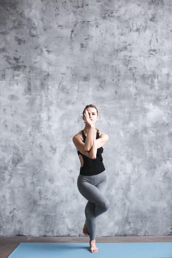 Retrato completo da mulher bonita nova que faz o exercício da ioga dentro foto de stock royalty free