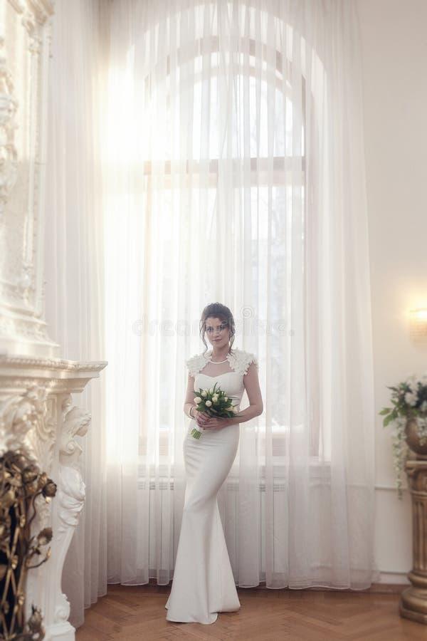 Retrato completo da noiva perto de uma grande janela fotos de stock royalty free