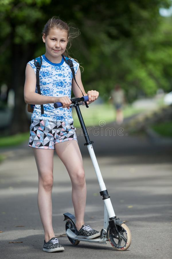 Retrato completo da posição preteen europeia da menina perto do 'trotinette' em uma estrada asfaltada foto de stock royalty free