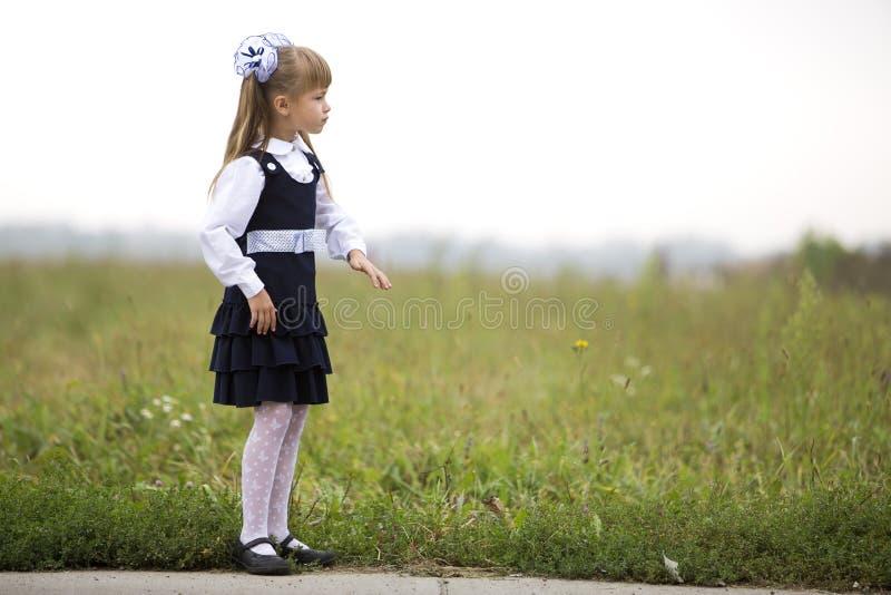Retrato completo da primeira menina pensativa s?ria ador?vel bonito do graduador na farda da escola e das curvas brancas no cabel fotografia de stock royalty free