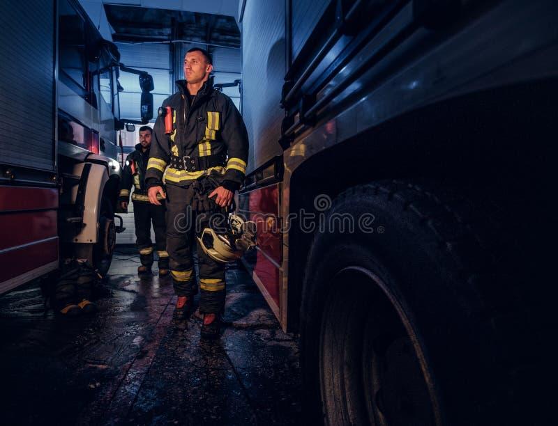Retrato completo de dois bombeiros corajosos no uniforme protetor que andam entre duas viaturas de incêndio na garagem do fotografia de stock