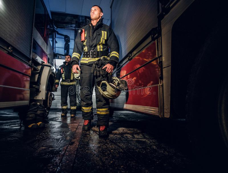 Retrato completo de dois bombeiros corajosos no uniforme protetor que andam entre duas viaturas de incêndio na garagem do imagem de stock