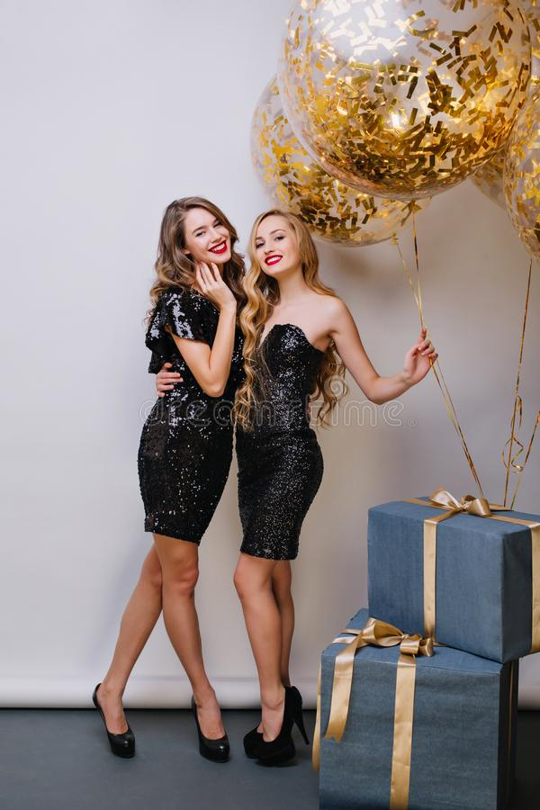 Retrato completo de duas meninas de surpresa que preparam-se para a festa de anos Foto interna da jovem mulher europeia atrativa imagens de stock