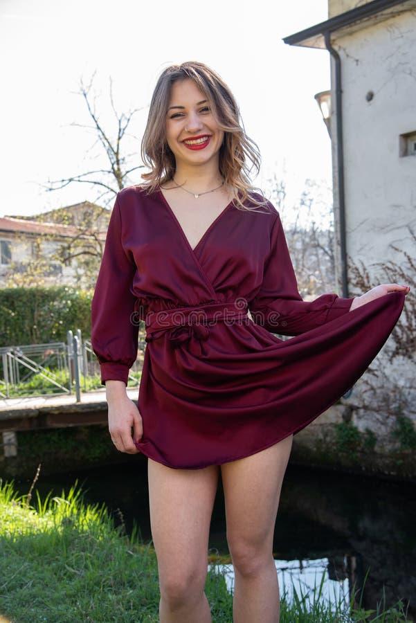 Retrato completo de uma menina loura com um vestido vermelho curto, jogando com sua saia que mostra seus pés foto de stock royalty free