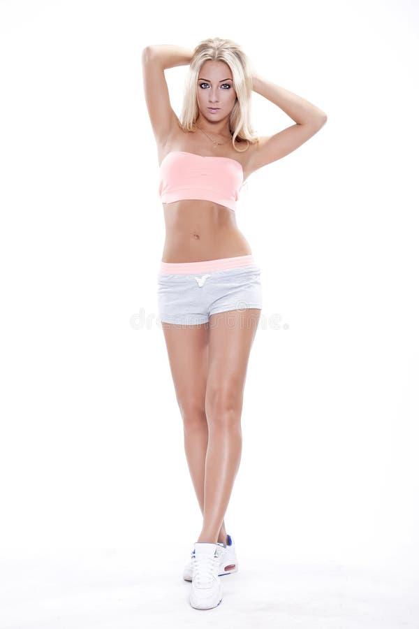 Retrato completo de uma mulher alegre nova que está no cinza fotografia de stock