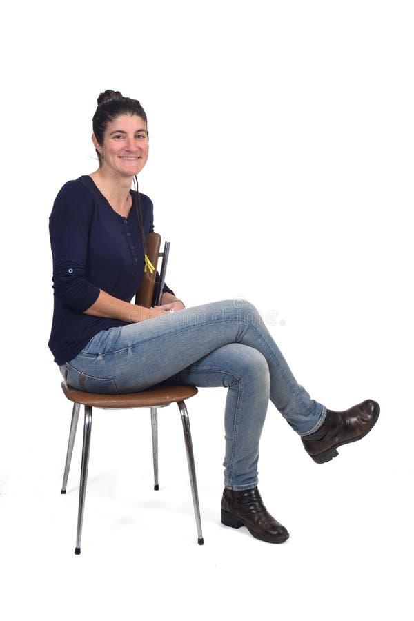 Retrato completo de uma mulher que senta-se em uma cadeira de pernas cruzadas e que olha a câmera fotos de stock royalty free