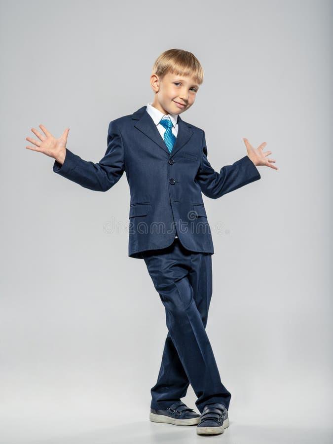 Retrato completo de un chico divertido con un traje de negocios azul, posando en el estudio Chico alegre vestido con traje formal fotografía de archivo libre de regalías