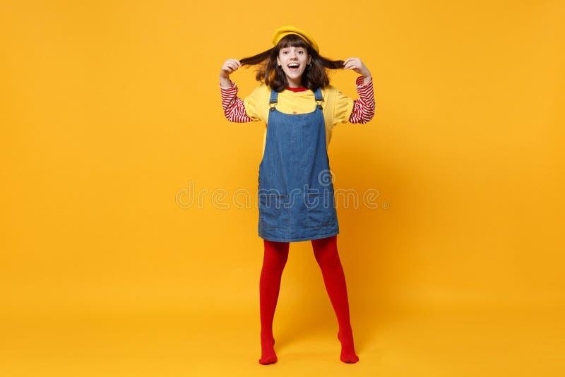 Retrato completo do comprimento do adolescente entusiasmado da menina na boina francesa, sundress da sarja de Nimes que mantêm o  imagem de stock