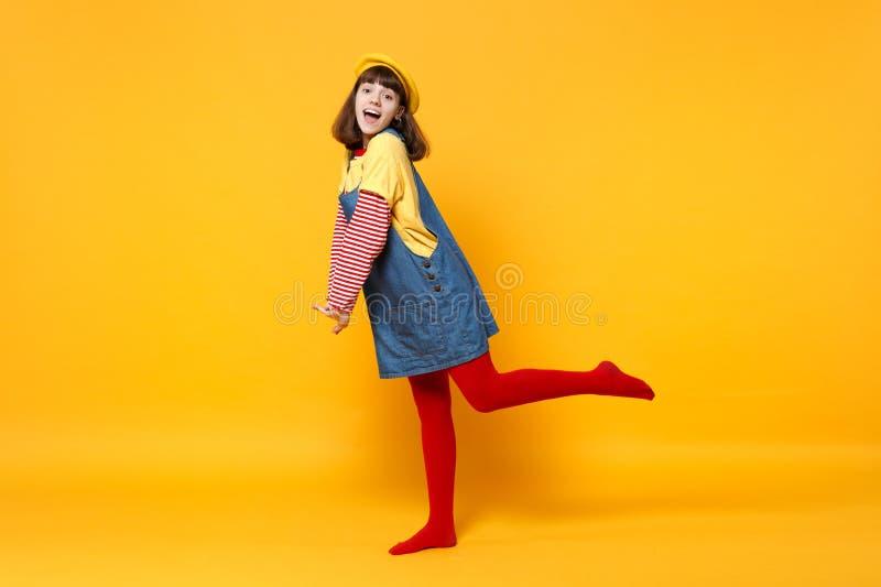 Retrato completo do comprimento do adolescente entusiasmado da menina na posição francesa dos sundress da boina e da sarja de Nim imagens de stock royalty free