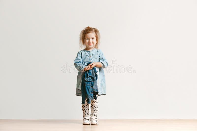 Retrato completo do comprimento da criança bonito na roupa à moda das calças de brim que olha a câmera e o sorriso imagens de stock