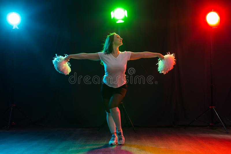 Retrato completo do comprimento da dança do líder da claque com pom-poms imagem de stock royalty free