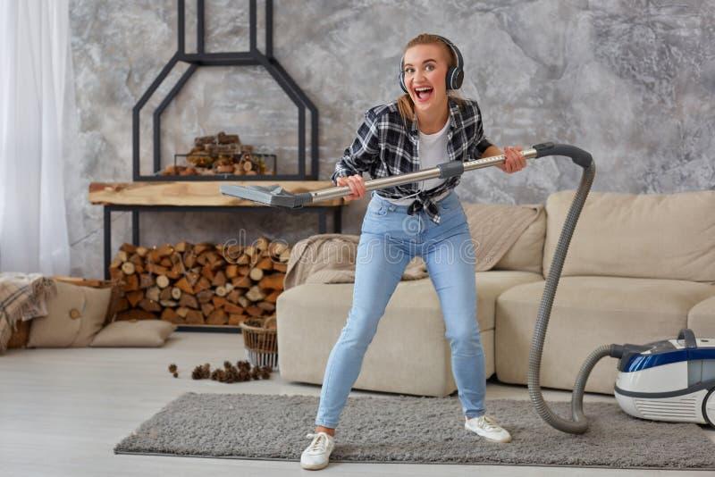 Retrato completo do comprimento da jovem mulher alegre 20s que escuta a música através dos fones de ouvido e que tem o divertimen fotografia de stock