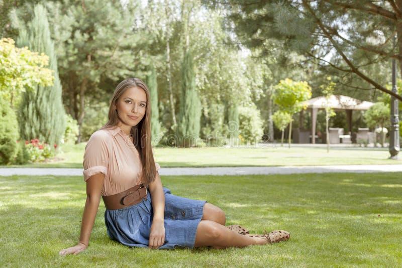 Retrato completo do comprimento da jovem mulher bonita que relaxa no parque imagens de stock royalty free